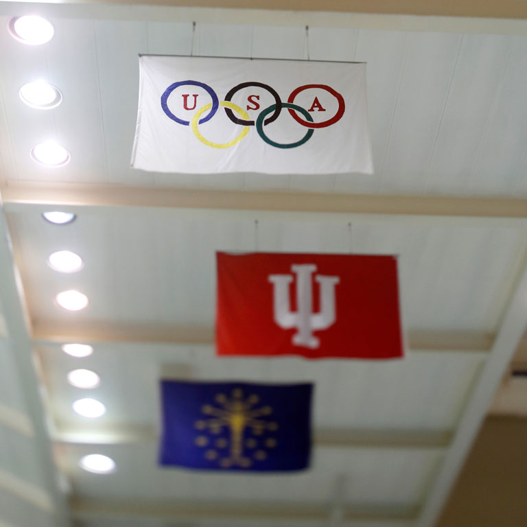 Flags honoring the Olympics, Indiana University and the state of Indiana hang from the ceiling of the Counsilman Billingsley Aquatics Center.